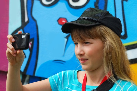 young girl taking photo with mobile phone on the trip photo