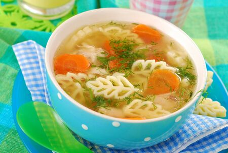 chicken soup: bowl of clear chicken soup with ear shape noodle for child