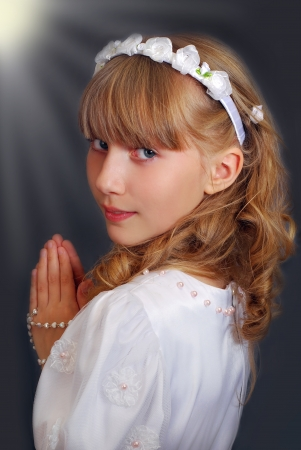 first communion: portrait of beautiful girl going to the first holy communion and posing in studio against dark background with lights