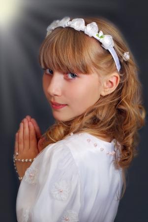 comunion: retrato de la hermosa niña de ir a la primera comunión y posando en estudio contra el fondo oscuro con luces Foto de archivo