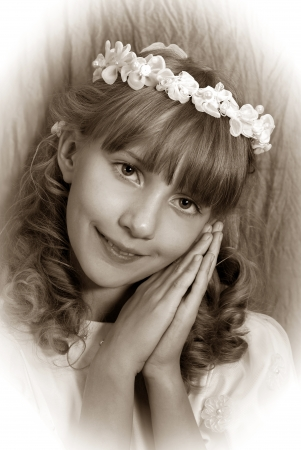 vintage portrait of beautiful girl going to the first holy communion and posing in studio (sepia) photo