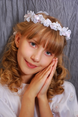 portrait of beautiful girl going to the first holy communion and posing in studio against dark background  photo