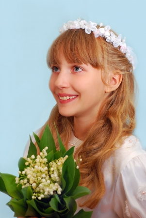 portrait of happy girl going to the first holy communion and posing in studio with bunch of lily of the valley flowers  photo
