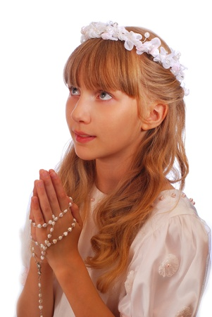 first communion: portrait of happy girl going to the first holy communion and posing in studio against white background