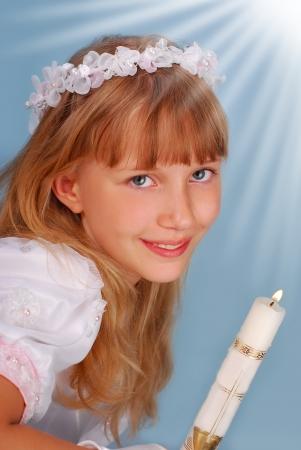 Portret van meisje naar de Eerste Heilige Communie met een kaars en poseren in de studio