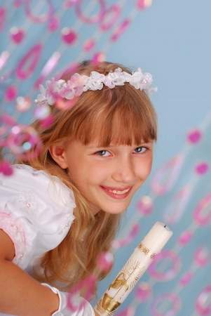 portrait of girl going to the first holy communion holding a candle and posing in studio  photo