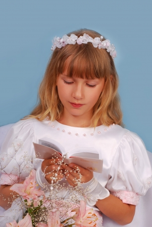 portrait of praying girl going to the first holy communion  and posing in studio  photo