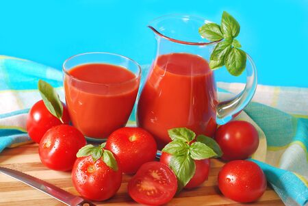 carafe: jug and glass full of freshly prepared tomato juice on wooden board against blue background Stock Photo