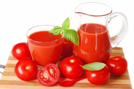 Krug und Glas voll mit frisch zubereiteten Tomatensaft auf Holzbrett vor weissem Hintergrund Standard-Bild