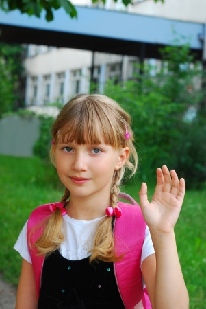 longhair: young girl going to school and waving hand for goodbye Stock Photo