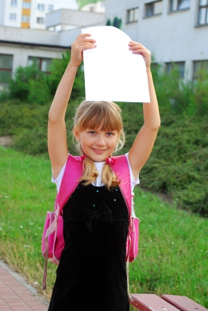 front end: young happy schoolgirl showing graduation certificate standing in front of the school Stock Photo