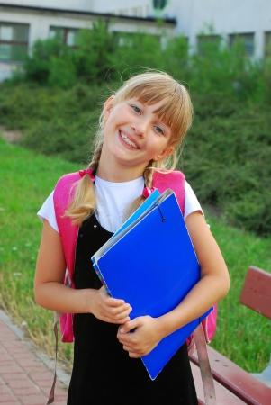 escuela primaria: permanente joven, colegiala feliz en frente de la escuela