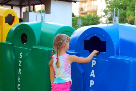 niños reciclando: niña arroja los residuos de papel en la bandeja especial de reciclaje de la basura Foto de archivo