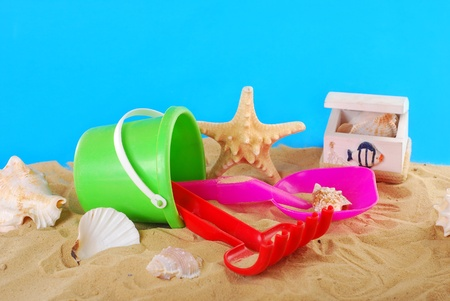 beach plastic toys-bucket,spade and rake lying on the sand with seashells photo