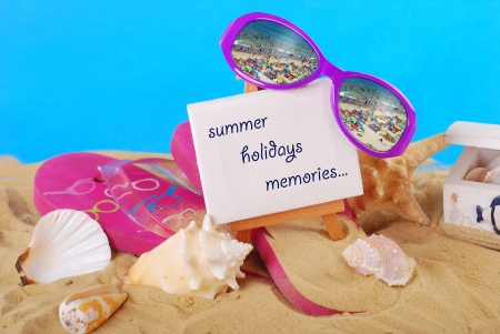 beach still life with greetings text written on easel ,flip-flop,seashells and seaside reflected in  sunglasses  photo