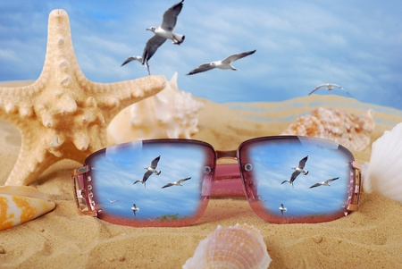 sunglasses lying on the beach with reflection of flying seagulls photo