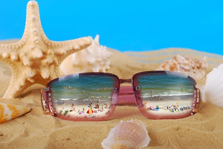 sunglasses lying on the beach with reflection of people on the seaside Stock Photo - 14562220