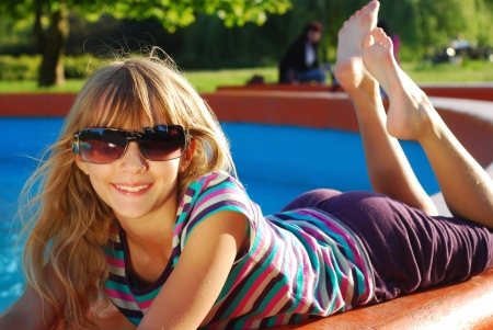 happy young girl in sunglasses lying in the park and relaxing in summer holidays photo