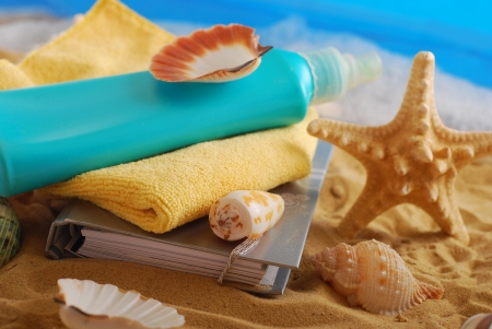 diary,suntan lotion,towel and seashells lying on the beach as summer holidays concept photo
