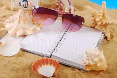 opened diary for writing summer holidays memories ,seashells and sunglasses lying on the beach  photo