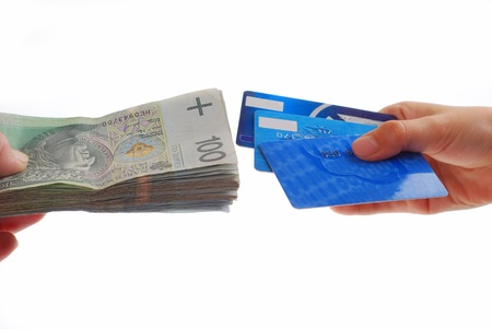 cash card: one hand holding stack of polish banknotes and second hand holding credit cards isolated on white