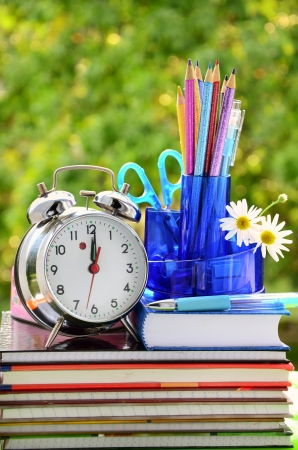 school equipment and alarm clock against green trees photo