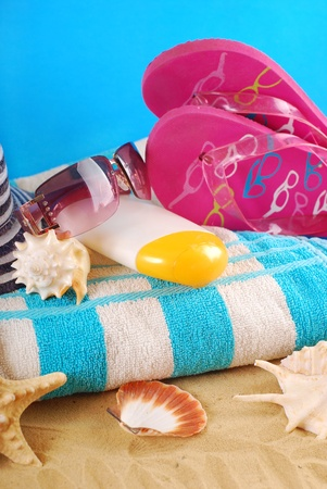 beach equipment with towel,sunglasses,suntan lotion,flip flops and seashells lying on sand photo