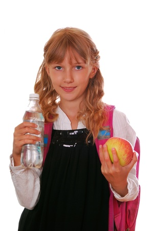 schoolgirl  holding in hand a bottle of water and an apple for healthy breakfast isolated on white photo