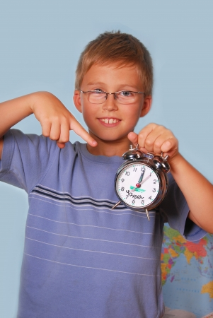 schoolboy holding retro alarm clock and showing on it against  blue background photo