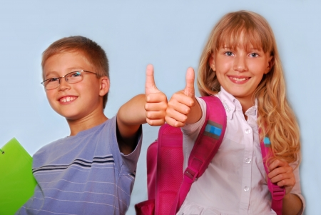 smiling young boy and girl going to school and showing thumbs up sign photo