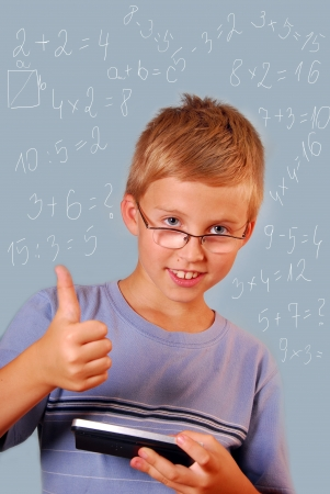 schoolboy holding calculator and showing thumb up against math blue background photo
