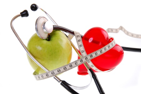 plastic heart: healthy diet concept with apple,stethoscope,plastic heart and measure tape isolated on white