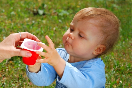 hungry baby girl taking yogurt from mother`s hand outdoor (focus on face) photo