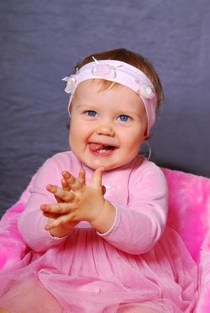 manos aplaudiendo: retrato de niña feliz en manos de color rosa vestido de palmas en el estudio