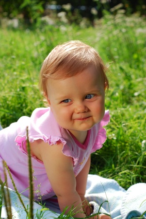 portrait of cute baby girl crawling on the grass photo