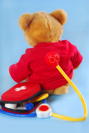 medical cabinet: teddy bear in red t-shirt sitting back with stethoscope and first aid kit Stock Photo