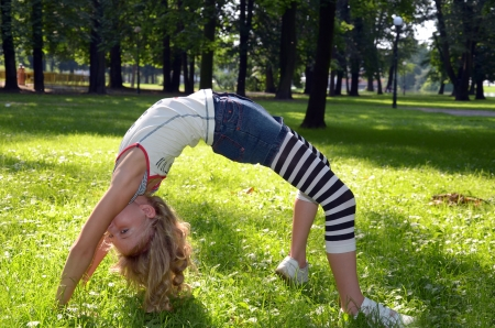 young girl  exercising in bridge pose in the park photo