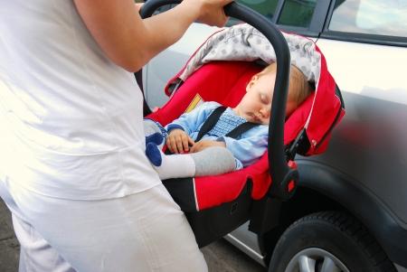 moeder die baby slaapt in het autostoeltje in de auto Stockfoto