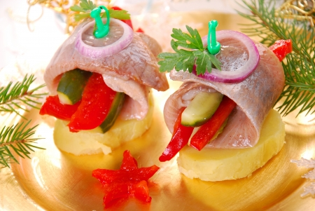gherkin: appetizer with rolled herring fillet stuffed with red pepper and gherkin on potato ring for christmas  Stock Photo