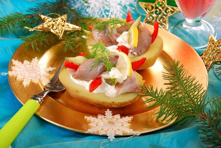 half fish: half of boiled potato with herring fillet,sour cream and cheese as appetizer for christmas