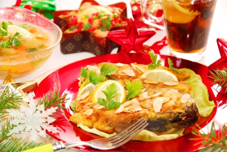 deep-fried carp with almonds flakes and other traditional polish dishes on christmas table