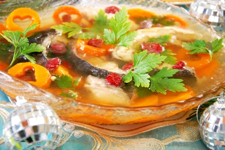 carp in jelly with carrot and cranberry as traditional polish dish on christmas table