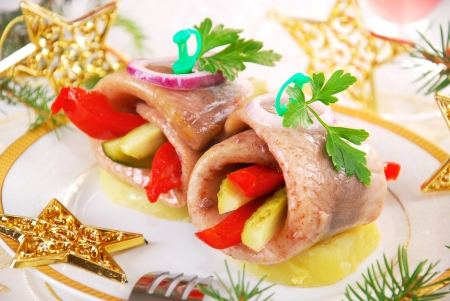 appetizer with rolled herring fillet stuffed with red pepper and gherkin on potato ring for christmas