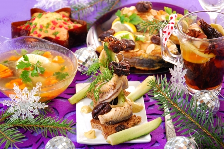 herring appetizer with prune and gherkin and other traditional polish dishes on christmas table Standard-Bild