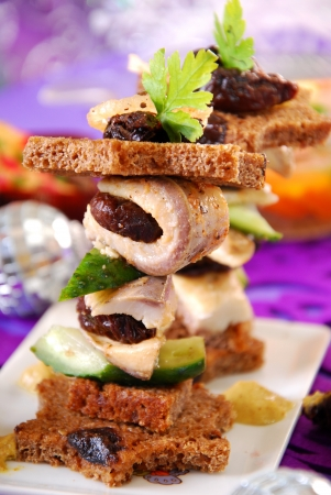 herring canapes with dark bread in star shape,prune and gherkin on christmas eve`s table photo
