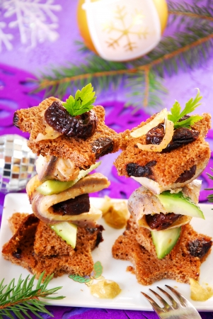 prune: herring canapes with dark bread in star shape,prune and gherkin on christmas eve`s table