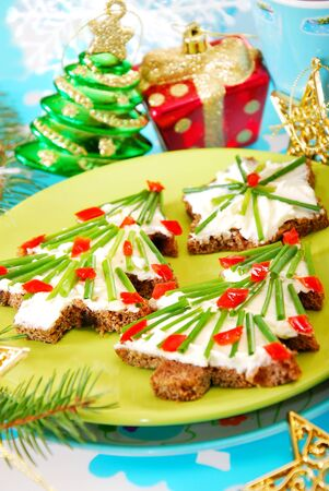 christmas tree and star shape sandwiches with dark bread,cheese and chive as breakfast for child