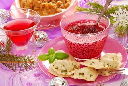 pierogi: clear red boorscht and ravioli (pierogi) filled with sauerkraut and mushrooms for traditional polish christmas Stock Photo