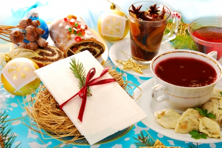 christmas dish: polish christmas eve table with white wafer on plate with hay and traditional dishes