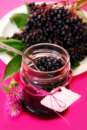 homemade: jar of homemade elderberry confiture and fresh fruits on pink background